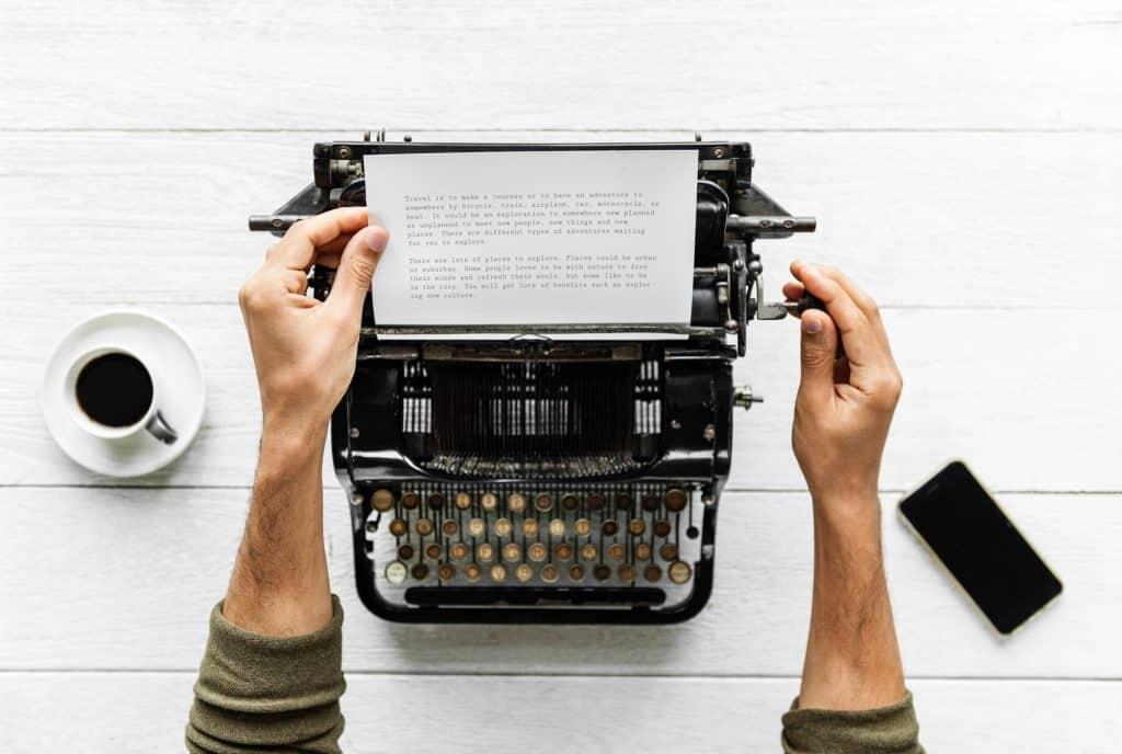 Mann betrachtet geschriebenen Text von einer alten Schreibmaschine