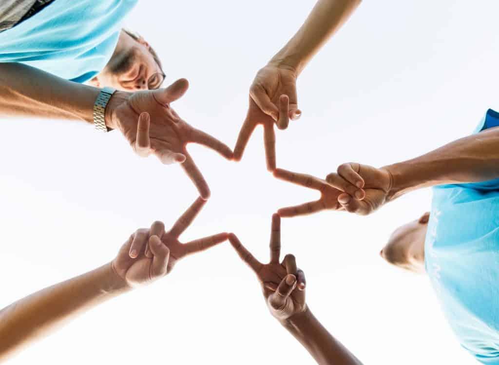 Menschen halten Hände mit Peace Zeichen mittig zu einem Stern zusammen