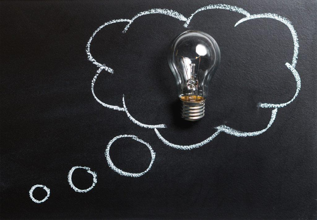 Glühbirne in gezeichneter Gedankenblase auf schwarzem Hintergrund