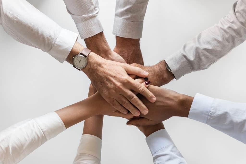 Acht Leute legen ihre Hände in der Mitte des Kreises aufeinander