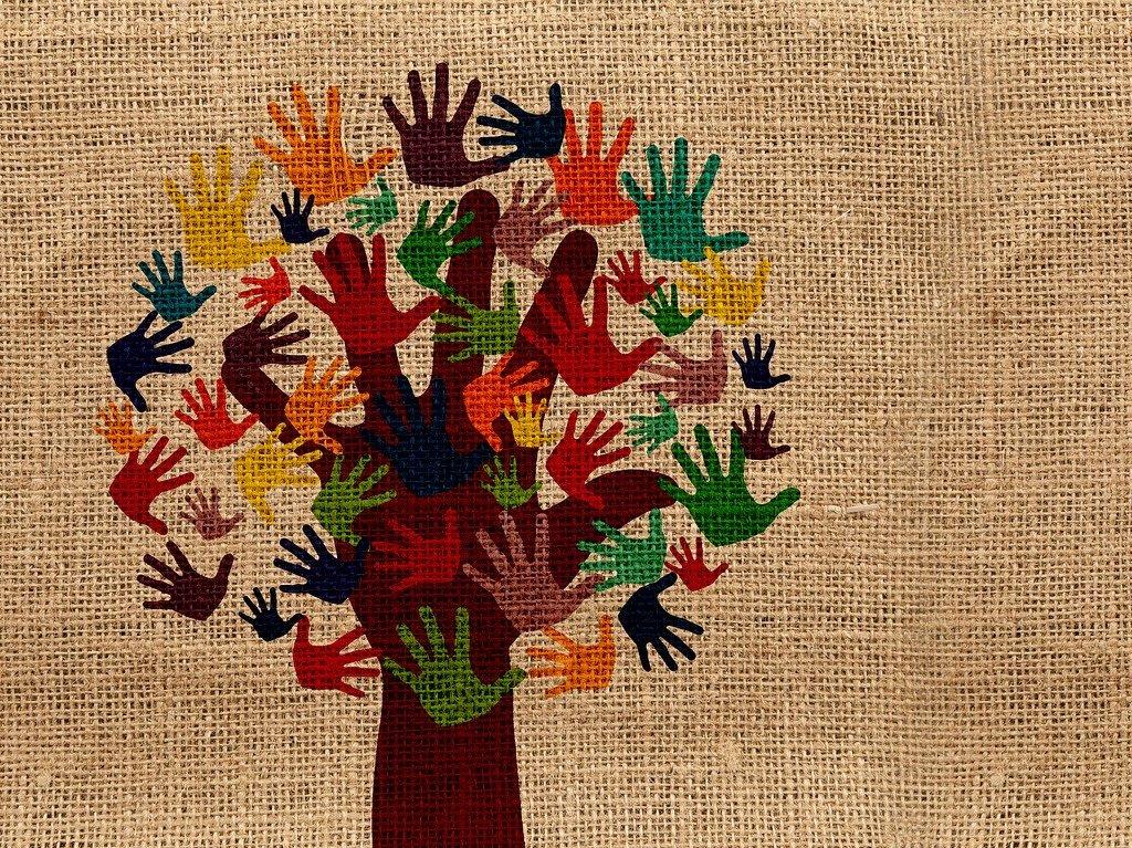Farbige Hände bilden auf einem Jutesack einen Baum mit Blättern